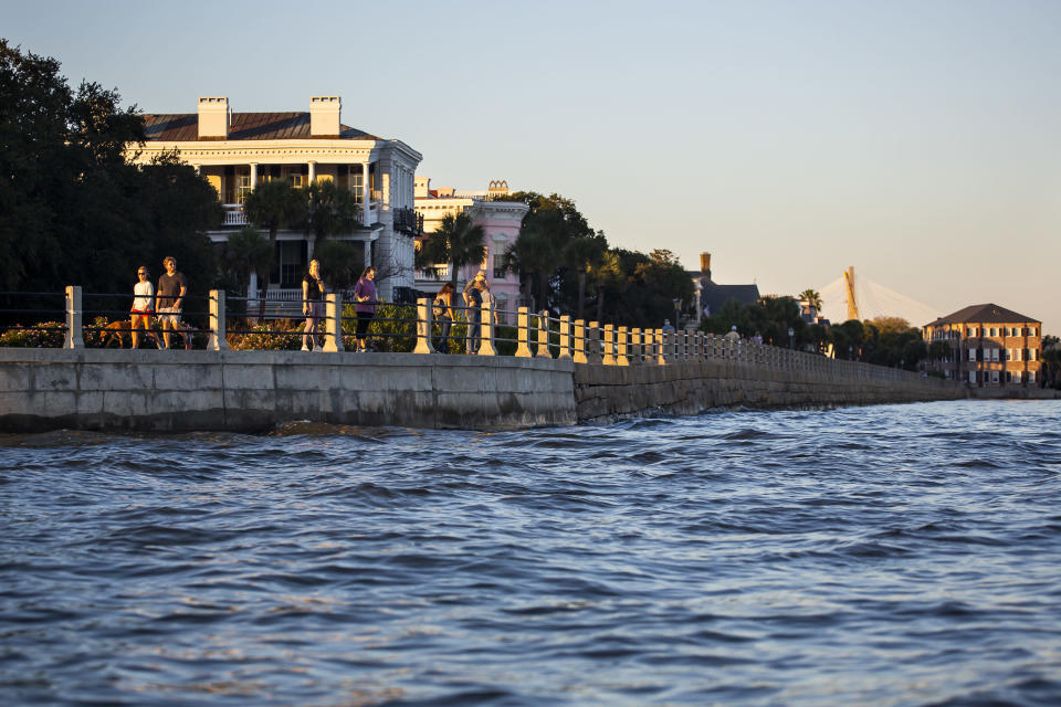 As high tide laps against the sea wall tourist walk down the Battery in Charleston, S.C. Friday, Nov. 13, 2020. Charleston has remained relatively unscathed this hurricane season. That means more time to mull a $1.75 billion proposal by the Army Corps of Engineers that features a sea wall along the city's peninsula to protect it from deadly storm surge during hurricanes. (AP Photo/Mic Smith)