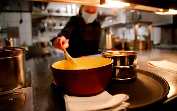 """A cooker wearing a protective face mask prepare a fondue, the beloved Swiss national dish of cheese melted down with white wine in a """"caquelon"""" pot heated by an open flame at Restaurant Marzilibruecke in Bern, on November 16, 2020. - As Switzerland contends with one of the worst coronavirus surges in Europe, the Swiss are gripped by one melting hot question: is it still safe to share a fondue? (Photo by STEFAN WERMUTH / AFP) / TO GO WITH AFP STORY BY AGNES PEDRERO AND VIDEO BY ELOI ROUYER (Photo by STEFAN WERMUTH/AFP via Getty Images) - STEFAN WERMUTH/AFP"""
