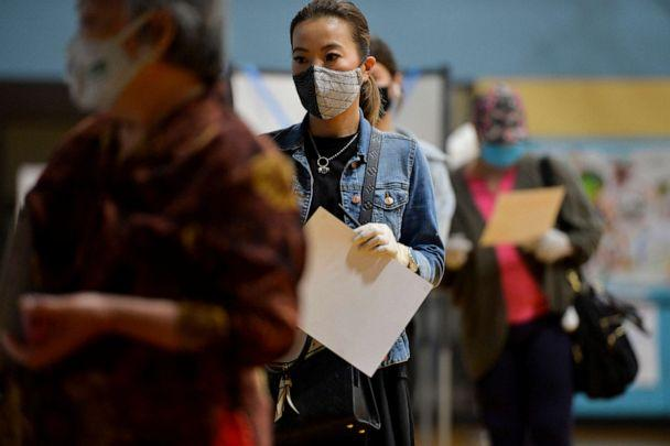 PHOTO: People wait in line to hand in their ballots to election officials after voting at a YMCA in Chinatown during the Massachusetts State Primary on Sept. 1, 2020, in Boston. (Joseph Prezioso/AFP via Getty Images)