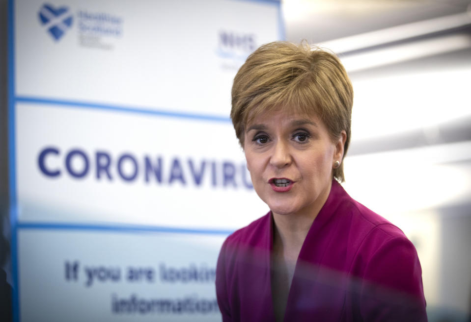 """Scotland's First Minister Nicola Sturgeon stands near a sign reading """"CORONAVIRUS"""" as she speaks during a visit to the NHS 24 contact centre at the Golden Jubilee National Hospital in Glasgow, Scotland, on March 4, 2020. - Up to one fifth of employees could be off work in Britain when the coronavirus outbreak peaks, the government said Tuesday outlining a new action plan. Britain had 51 confirmed cases of COVID-19 as of 9:00 am (0900 GMT), an increase of 12 in 24 hours, as Prime Minister Boris Johnson warned the count was """"highly likely"""" to keep rising. (Photo by Jane Barlow / POOL / AFP) (Photo by JANE BARLOW/POOL/AFP via Getty Images)"""