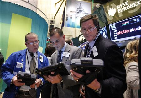 Traders work in front of a trading board showing Shutterstock Inc on the floor of the New York Stock Exchange