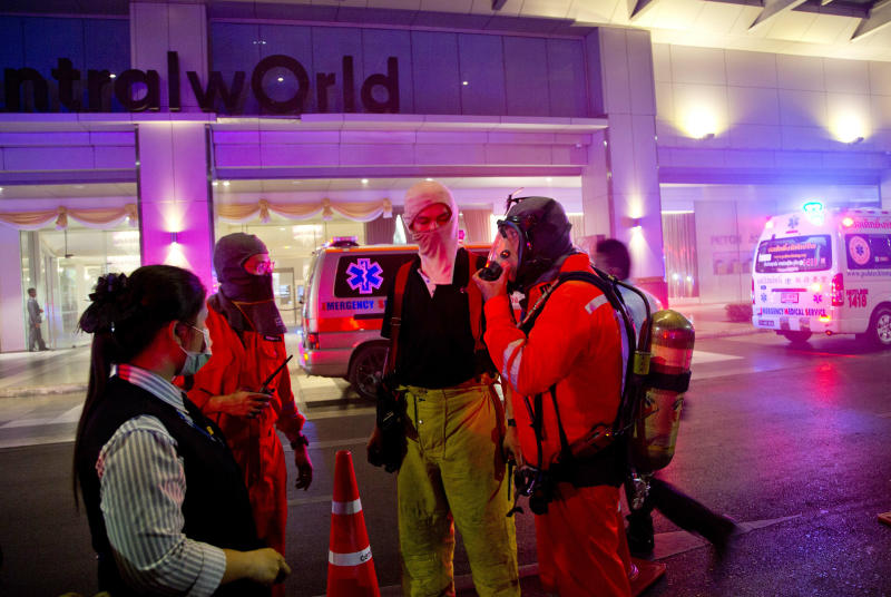 Firefighters adjust their smoke-masks as they prepare to enter the scene of a fire at the Central World mall complex in Bangkok, Thailand, Wednesday, April 10, 2019. A fire had broken out at the major mall complex in Thailand's capital, with initial reports from Thai emergency services saying it has caused numerous fatalities. (AP Photo/Gemunu Amarasinghe)
