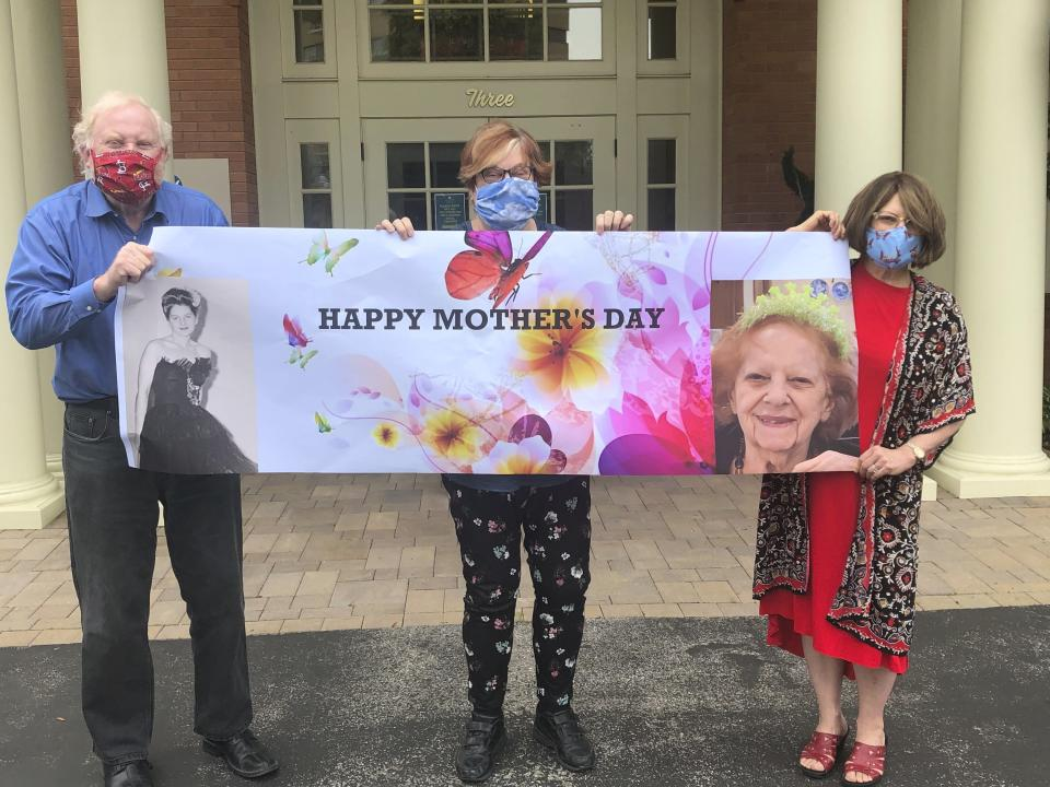 """This May 3, 2020, photo released by Shelly Solomon shows, from left, Steve Turner and his sisters, Carla Paull and Lisa Fishman, holding up a Mother's Day banner emblazoned with images of their mom, Beverly Turner, in front of her assisted living facility in Ladue, Missouri. They were """"practicing"""" how their Mother's Day surprise will look on the holiday as their mother peers down from a window. Isolation due to the coronavirus outbreak has led mothers and offspring to find creative ways to celebrate. (Shelly Solomon via AP)"""
