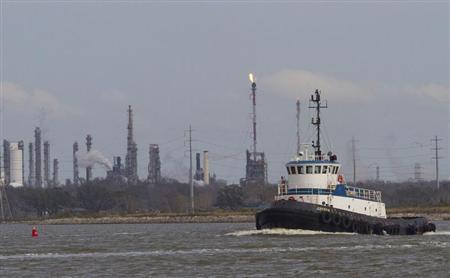A tug boat navigates the Houston ship channel with a flare from an oil refinery and storage facility in the background south of downtown Houston