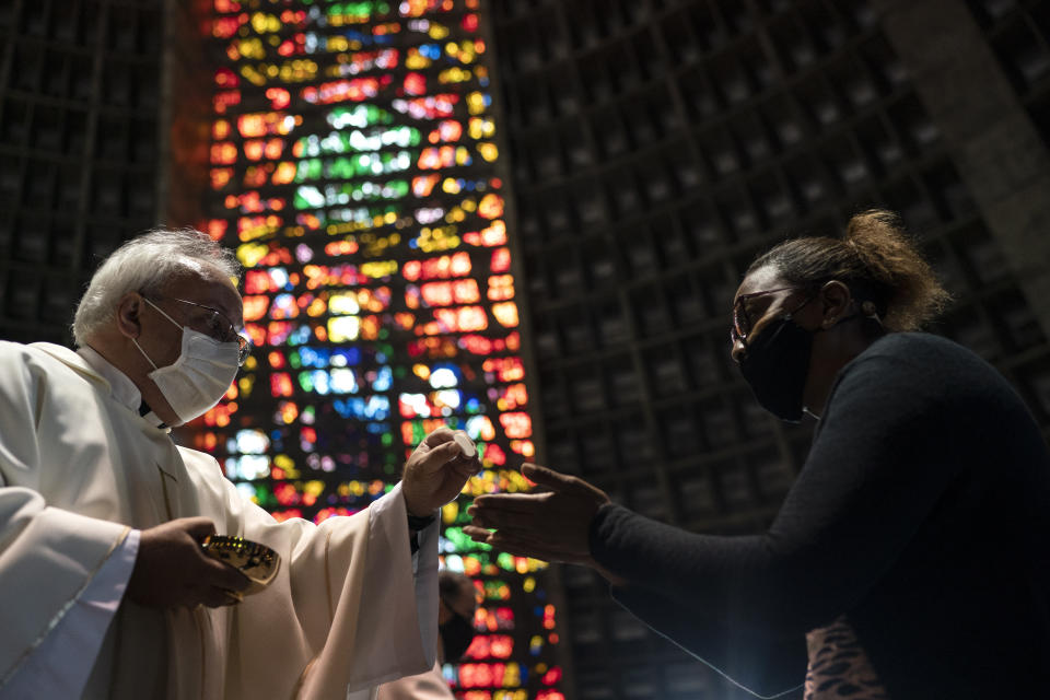 Wearing a protective mask a priest offers a communion wafer to a faithful during a Mass at the Metropolitan Cathedral in Rio de Janeiro, Brazil, Saturday, July 4, 2020. Following an easing of restrictions related to COVID-19, the Catholic church in Rio celebrated its first Mass with 30% of its worshippers, while observing preventive measures to avoid spreading the new coronavirus. (AP Photo/Leo Correa)