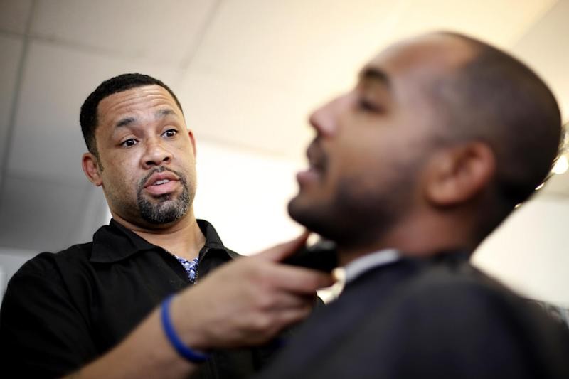 """Dorsey Jackson trims Be-Emnet Zegeye's beard at his establishment Jackson's Barbershop, Friday, May 11, 2012, in Ardmore, Pa. Like many black Americans, Dorsey Jackson does not believe in gay marriage, but he wasn't disillusioned when Barack Obama became the first president to support it. The windows of his suburban Philadelphia barbershop still display an """"Obama 2012"""" placard and another that reads """"We've Got His Back."""" (AP Photo/Matt Rourke)"""