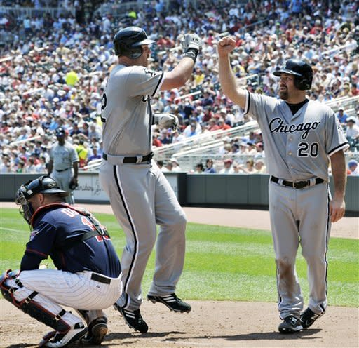 Chicago White Sox Kevin Youkilis, right, celebrates with Adam Dunn after Dunn's three-run home run off Minnesota Twins pitcher Nick Blackburn in the fifth inning of a baseball game Wednesday, June 27, 2012 in Minneapolis. At left is Twins catcher Ryan Doumit. (AP Photo/Jim Mone)