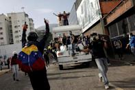 Demonstrators stand on a truck they want to use as a barricade while clashing with riot security forces during a rally against Venezuela's President Nicolas Maduro in Caracas, Venezuela, May 31, 2017. REUTERS/Carlos Garcia Rawlins