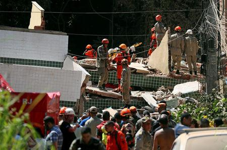 Rescue workers are seen at the site of a collapsed building in Muzema community, Rio de Janeiro, Brazil April 12, 2019. REUTERS/Ricardo Moraes