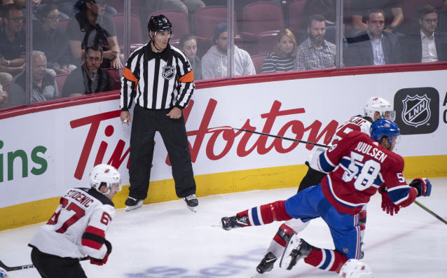 In this photo taken Sept. 17, 2018, referee Wes McCauley, top, keeps an eye on the play as the Montreal Canadiens face the New Jersey Devils during third-period preseason NHL hockey game action in Montreal. An informal poll of NHL players leaves no doubt as to who the most popular referee is: Veteran McCauley. (Paul Chiasson/The Canadian Press via AP)