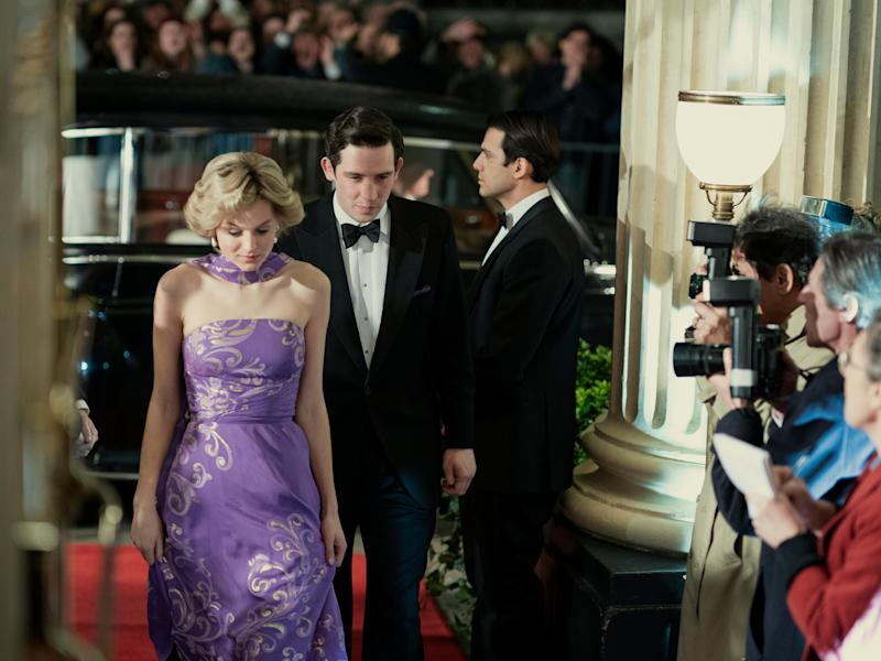 Pincess Diana (Emma Corrin) and Prince Charles (Josh O'Connor) are seen walking by a line of photographersOllie UptonNetflix