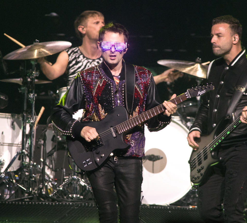 """Dominic Howard, drummer, Matt Bellamy, center, and Chris Wolstenholme of the band Muse perform in concert during their """"Simulation Theory World Tour"""" at The Wells Fargo Center on Sunday, April 7, 2019, in Philadelphia. (Photo by Owen Sweeney/Invision/AP)"""