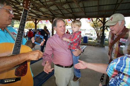 Democratic Alabama U.S. Senate candidate Doug Jones greets supporters holding a child while campaigning at an outdoor festival in Grove Hill, Alabama.   REUTERS/Mike Kittrell
