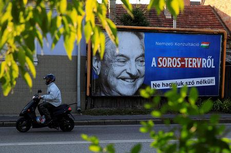 FILE PHOTO: A man rides his moped past a government billboard in Szolnok