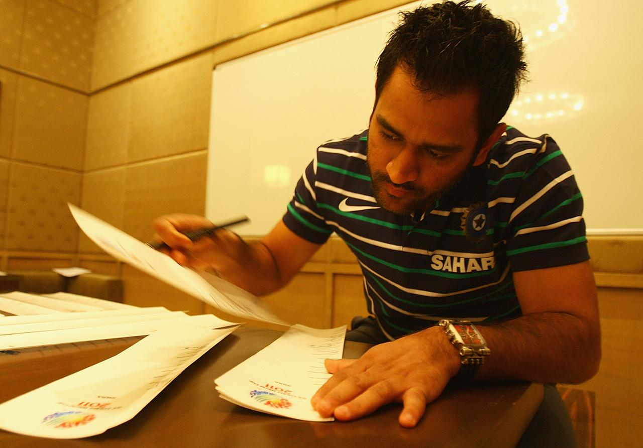 BANGALORE, INDIA - FEBRUARY 11:  Mahendra Singh Dhoni, captain of India, signs bat stickers during a portrait session ahead of the 2011 ICC World Cup at the ITC Gardenia on February 11, 2011 in Bangalore, India.  (Photo by Matthew Lewis/Getty Images)