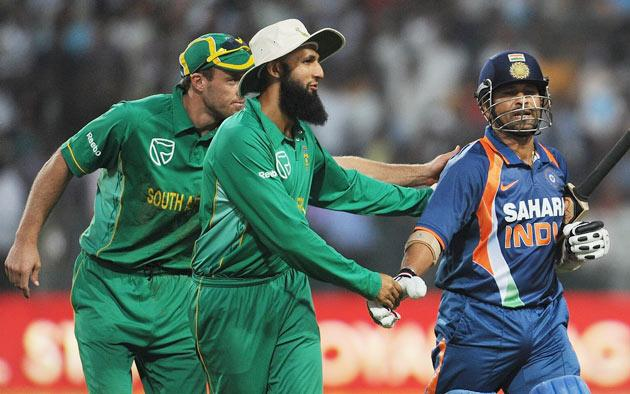 Indian cricketer Sachin Tendulkar (R) is congratulated by South African cricketers Hashim Amla (C) and Alvero Petersen (L) for scoring a world record breaking double century (200 runs) during the second One Day International (ODI) cricket match at the Captain Roop Singh Stadium in Gwalior on February 24, 2010. India played South Africa and finished with 401 runs for the loss of three wickets.  AFP PHOTO/ MANAN VATSYAYANA