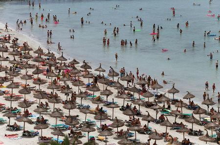 Tourists crowd Palma de Mallorca's Arenal beach on the Spanish Balearic island of Mallorca July 25, 2014. REUTERS/Enrique Calvo/File Photo