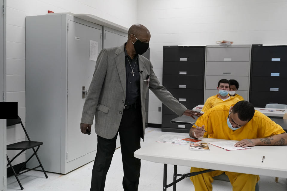 """The Rev. Burton Barr works with inmates at the St. Louis City Justice Center on Thursday, May 20, 2021. He calls himself """"the hoodlum preacher"""" and he goes to the jail twice a week to try to save people from the addiction that consumed his life for 22 years. The face of addiction then was inner-city Black people like him, and they were criminalized. Barr once tried to tally the number of times he went to jail, and he stopped counting at 30. (AP Photo/Brynn Anderson)"""