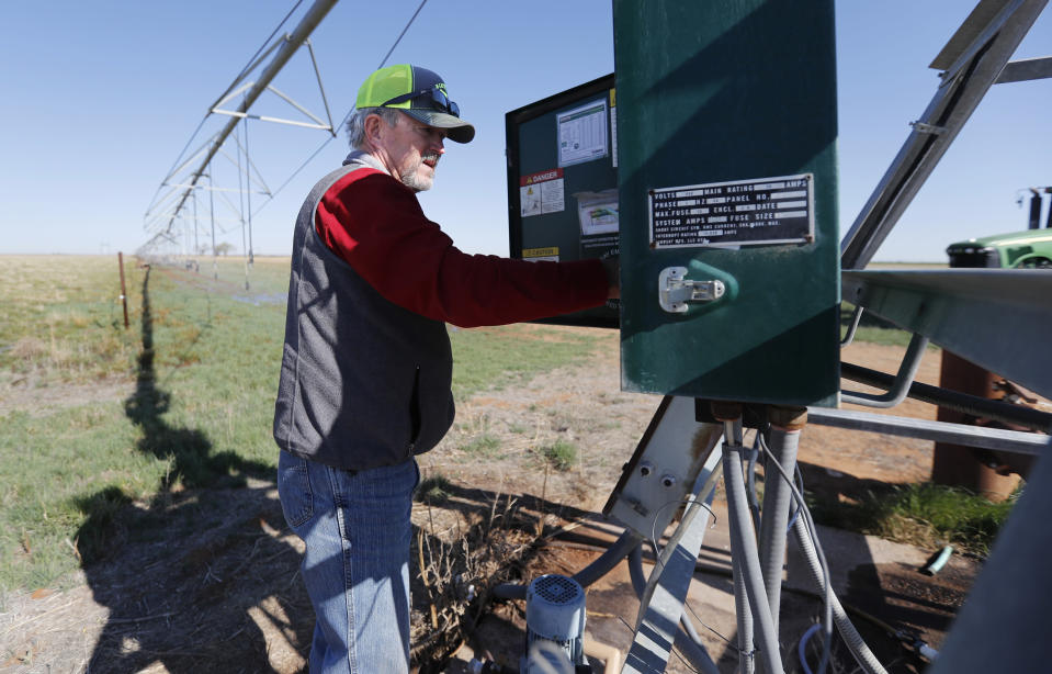 Tim Black adjusts the water application rate on a pivot for a newly planted field on his Muleshoe, Texas, farm on Monday, April 19, 2021. The longtime corn farmer now raises cattle and plants some of his pasture in wheat and native grass – and rations water use -- because the Ogallala Aquifer is drying up. (AP Photo/Mark Rogers)