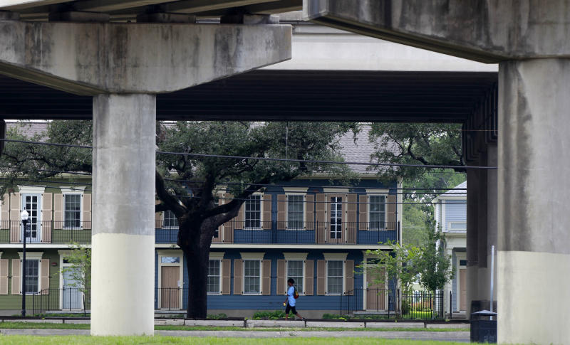 A woman walks past new public assisted housing where the Lafitte housing projects once stood, with the elevated Interstate 10 on Claiborne Ave. in the foreground in New Orleans, Thursday, Aug. 23, 2012. The face of New Orleans is changing: Seven years after Hurricane Katrina the city many said would not recover is racially more diverse, and whiter, younger and richer; indicators not of failure but its success at reinventing itself. In fact, the city is experiencing a boom, and even gentrifying.(AP Photo/Gerald Herbert)