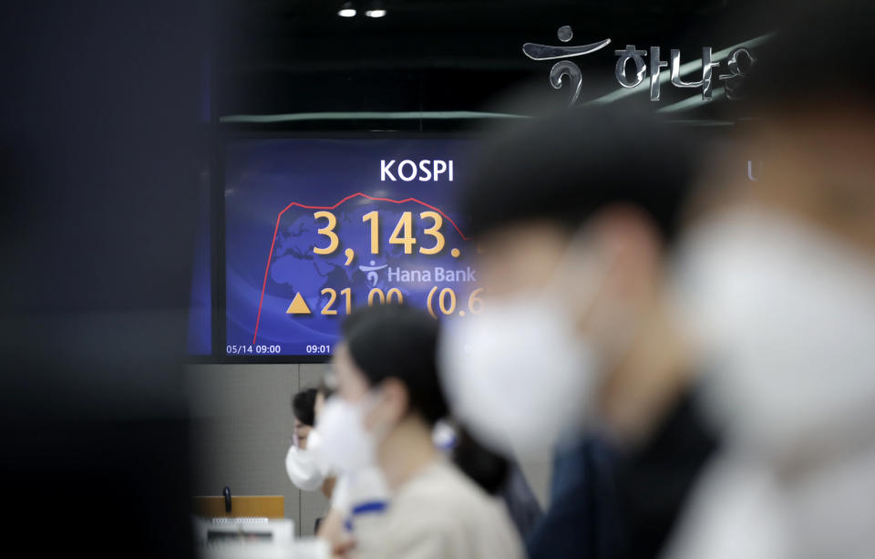 A currency trader watch computer monitors near the screen showing the Korea Composite Stock Price Index (KOSPI) at the foreign exchange dealing room in Seoul, South Korea, Friday, May 14, 2021. Asian shares rose Friday after Wall Street put the brakes on a three-day losing streak with a broad stock market rally powered by Big Tech companies and banks. (AP Photo/Lee Jin-man)