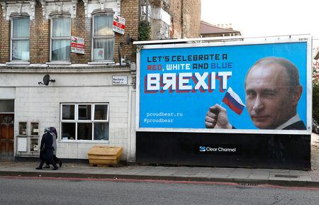 People walk past a billboard poster in London, Britain, November 8, 2018. REUTERS/Peter Nicholls