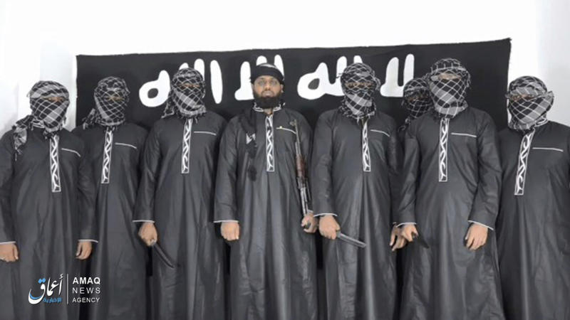 This undated image posted by the Islamic State group's Aamaq news agency on Tuesday, April 23, 2019, purports to show Mohammed Zahran, a.k.a. Zahran Hashmi, center, the man Sri Lanka says led the Easter attack that killed over 300 people, as well as other attackers. Sri Lankan authorities have blamed the militant Muslim group National Thowfeek Jamaath for the attack. The Islamic State group released the photo Tuesday to assert its claim on the assault. (Aamaq news agency via AP)