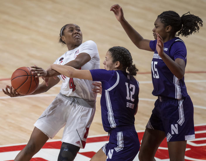 Nebraska's Sam Haiby (4) gis fouled by Northwestern's Veronica Burton (12) in the fourth quarter as Northwestern's Courtney Shaw (15) looks on during an NCAA college basketball game Thursday, Dec. 31, 2020, in Lincoln, Neb. (Francis Gardler/Lincoln Journal Star via AP)