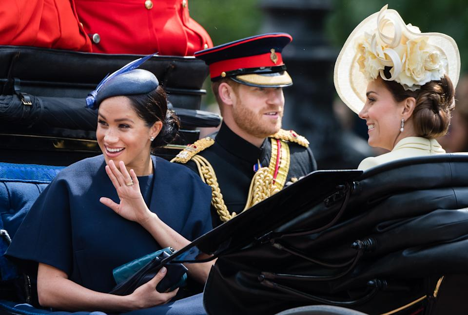 Prince Harry, the Duchess of Sussex and the Duchess of Cambridge ride by carriage down the Mall during Trooping The Colour. [Photo: Getty[