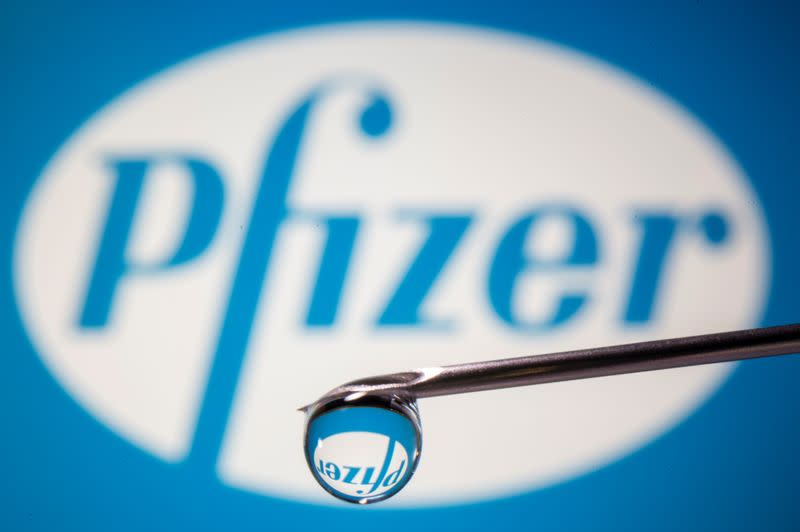 Pfizer's logo is reflected in a drop on a syringe needle in this illustration
