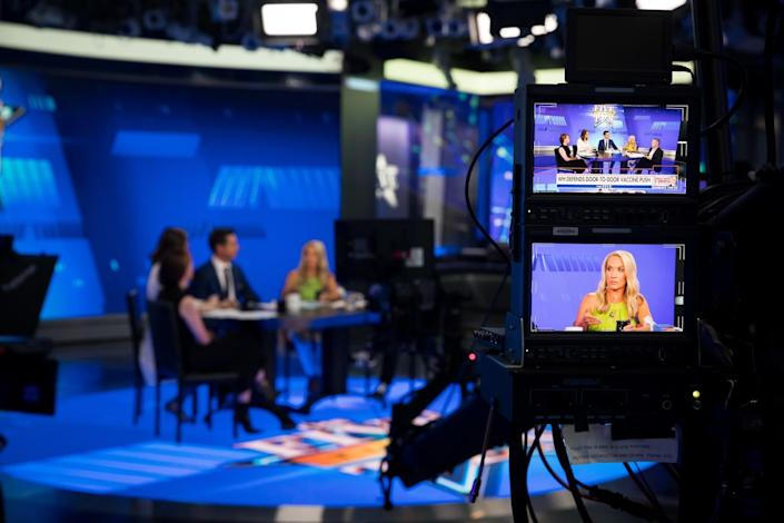 A woman is seen on a TV monitor as she and her show cohosts talk at a table in the background.