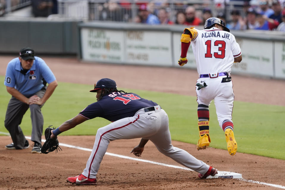 Atlanta Braves' Ronald Acuna Jr. (13) beats the throw to Washington Nationals first baseman Josh Bell (19) for an infield single in the first Inning of a baseball game Monday, May 31, 2021, in Atlanta. (AP Photo/John Bazemore)