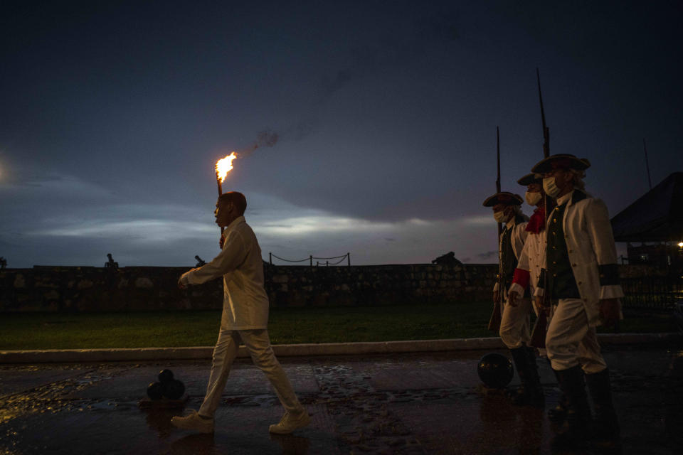 Soldiers dressed in period uniforms attend the nightly cannon ceremony at San Carlos de la Cabaña Fortress in Havana, Cuba, late Thursday, June 24, 2021. ThE blast originally signified the closing of the city gates and the lifting of the harbor chain to secure the city, and now during the COVID-19 pandemic, it marks the start of the nightly curfew put in place to help contain the spread of the virus. (AP Photo/Ramon Espinosa)