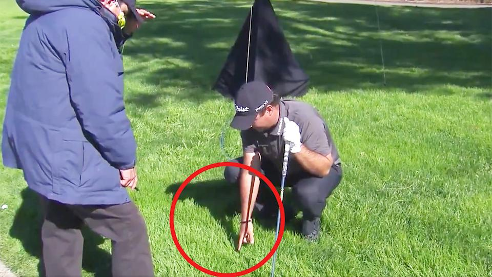 Patrick Reed (pictured right) pointing to the position where his ball landed to a rule official during the Farmers Insurance Open.