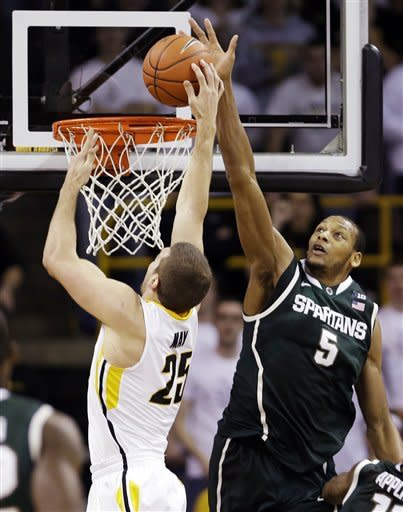 Michigan State center Adreian Payne (5) tries to block a shot by Iowa forward Eric May during the first half of an NCAA college basketball game, Thursday, Jan. 10, 2013, in Iowa City, Iowa. (AP Photo/Charlie Neibergall)