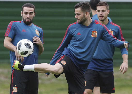 Spain's Dani Carvajal, left, looks as Spain's Nacho, center, kicks the ball during the official training on the eve of the group B match between Morocco and Spain at the Mirny stadium in Kaliningrad, Russia, Sunday, June 24, 2018. (AP Photo/Czarek Sokolowski)