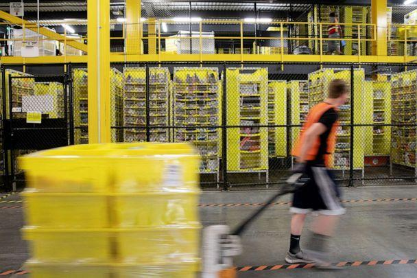 PHOTO: An employee pulls a pallet jack carrying plastic crates past goods in storage units at the Amazon.com Inc. fulfillment center in Robbinsville, N.J., June 7, 2018. (Bloomberg via Getty Images, FILE)