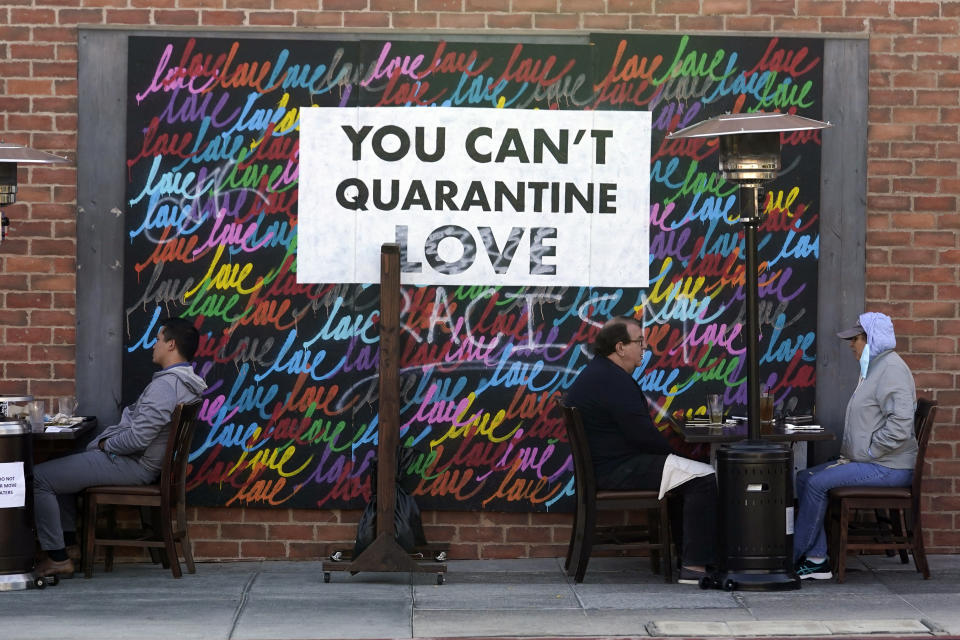 "A COVID-19-themed mural reads ""You Can't Quarantine Love,"" outside of a restaurant, Monday, Nov. 23, 2020, in Santa Monica, Calif. (AP Photo/Marcio Jose Sanchez)"
