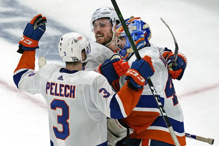New York Islanders center Casey Cizikas (53) and defenseman Adam Pelech (3) celebrate with Islanders goaltender Semyon Varlamov (40) after they defeated the Boston Bruins 5-4 in Game 5 of an NHL hockey second-round playoff series, Monday, June 7, 2021, in Boston. (AP Photo/Elise Amendola)