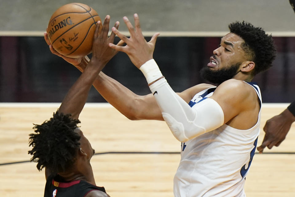 Miami Heat forward Jimmy Butler, left, and Minnesota Timberwolves center Karl-Anthony Towns (32) battle for a ball during the first half of an NBA basketball game, Friday, May 7, 2021, in Miami. (AP Photo/Wilfredo Lee)