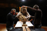 Workers handle a bust of Charles Le Brun by French sculptor Antoine Coysevox, in the Louvre museum, in Paris, Wednesday, Feb. 17, 2021. It's uncertain when the Louvre will reopen, after being closed on Oct. 30 in line with the French government's virus containment measures. But those lucky enough to get in benefit from a rarified private look of collections covering 9,000 years of human history -- with plenty of space to breathe. (AP Photo/Thibault Camus)
