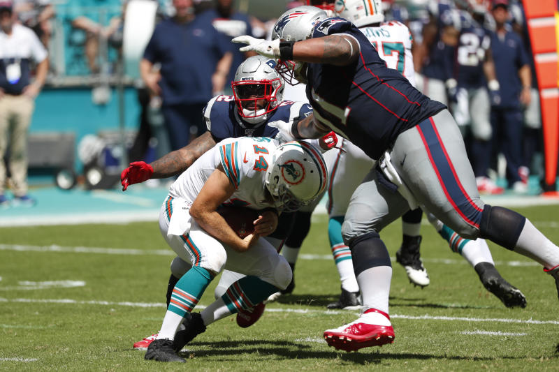 Miami Dolphins quarterback Ryan Fitzpatrick (14) ducks asNew England Patriots outside linebacker Elandon Roberts (52) and defensive tackle Danny Shelton (71) close in for a sack, during the second half at an NFL football game, Sunday, Sept. 15, 2019, in Miami Gardens, Fla. (AP Photo/Wilfredo Lee)