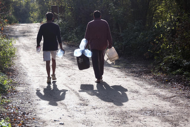 Migrants carry empty water canisters near the Vucijak refugee camp outside Bihac, northwestern Bosnia, Monday, Oct. 21, 2019.  Authorities in the town of Bihac on Monday stopped the delivery of water supplies to the Vucjak camp saying they want to draw attention to the problems in the camp set up on a former landfill and near mine fields from the 1992-95 war. (AP Photo/Eldar Emric)