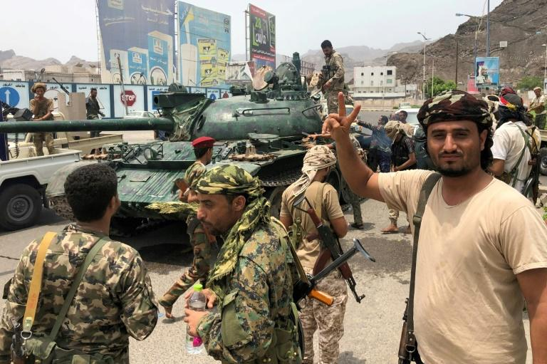Yemeni supporters of the southern separatist movement pose for a picture with a tank they confiscated from a military barracks in Aden where they have been fighting other forces loyal to the internationally recognised government