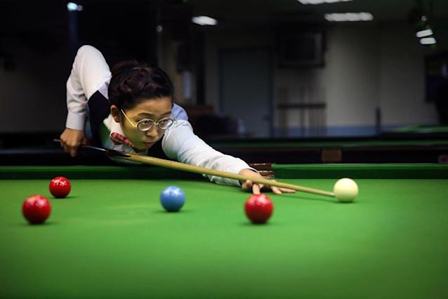 Hong Kong snooker player Ng On-Yee plays a shot during a game at a snooker hall in Hong Kong on January 27, 2016 (AFP Photo/Isaac Lawrence)