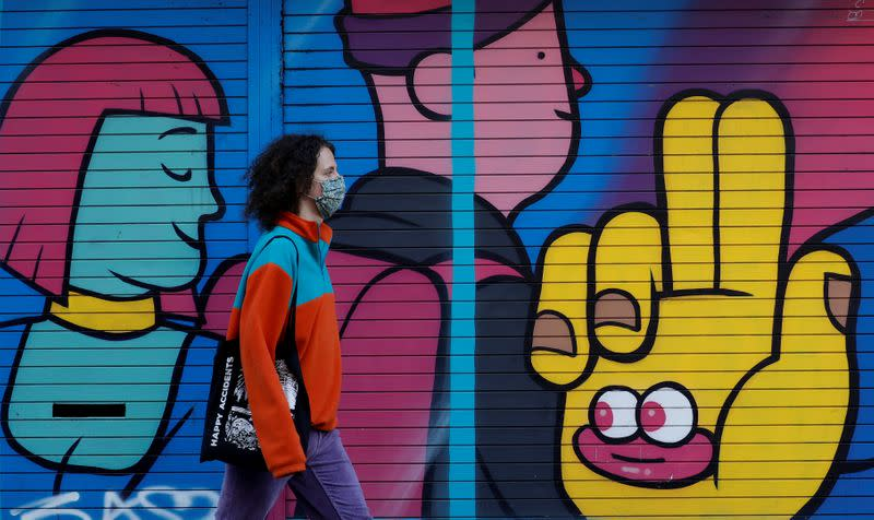 FILE PHOTO: A woman wears a face mask as she walks past a mural on a closed shop following the outbreak of the coronavirus disease (COVID-19) in Manchester, Britain