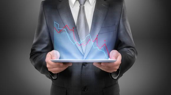 Person in suit holding tablet indicating downward-sloping chart.