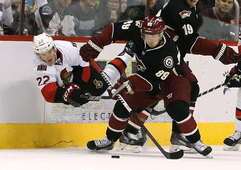 Phoenix Coyotes' Mikkel Boedker (89), of Denmark, tries to keep control of the puck as Ottawa Senators' Erik Condra (22) dives to hit the stick of Boedker during the first period in an NHL hockey game Tuesday, Oct. 15, 2013, in Glendale, Ariz. (AP Photo/Ross D. Franklin)