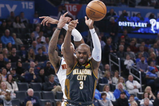 Oklahoma City Thunder guard Chris Paul (3) reaches for a rebound with Denver Nuggets forward Torrey Craig, rear, in the first half of an NBA basketball game Friday, Feb. 21, 2020, in Oklahoma City. (AP Photo/Sue Ogrocki)