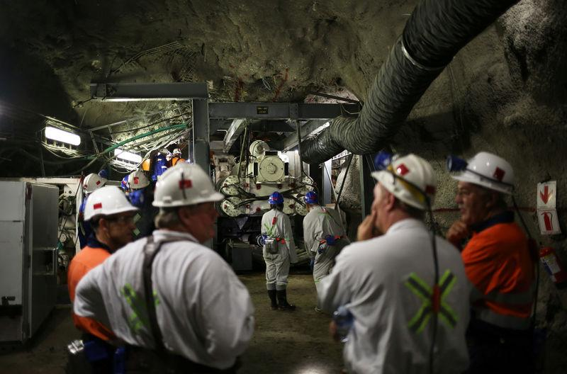 Mine workers are seen in front of a giant drill-cum-vacuum cleaner that accelerates drilling at an underground tunnel at Cullinan mine outside Pretoria, northeast of Johannesburg